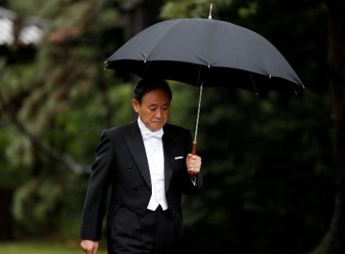 FILE PHOTO: Japan's Chief Cabinet Secretary Yoshihide Suga arrives at the ceremony site where Emperor Naruhito will report the conduct of the enthronement ceremony at the Imperial Sanctuary inside the Imperial Palace in Tokyo, Japan October 22, 2019. REUTERS/Kim Hong-ji
